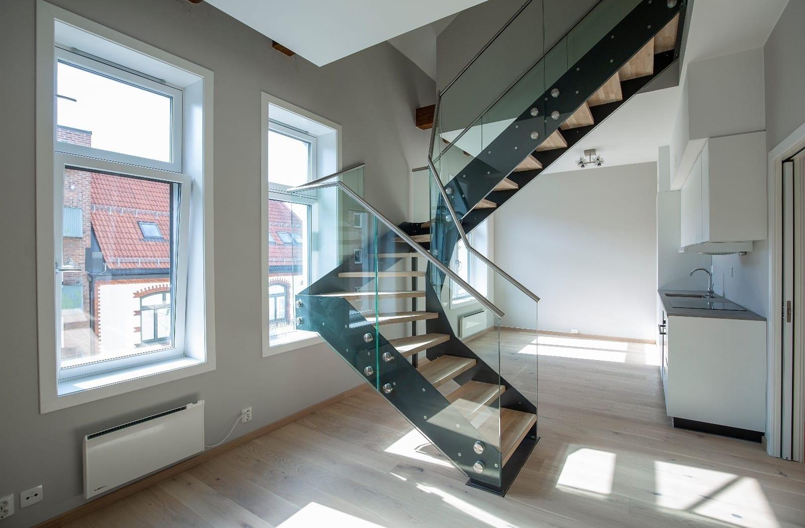 Åpen stue-kjøkken-løsning med stilig trapp opp til soverommene